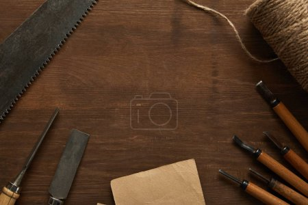 Photo for Top view of aged carpentry tools and twine near blank vintage paper on wooden table - Royalty Free Image