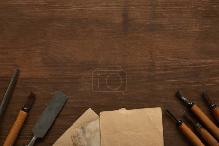 Photo for Top view of aged carpentry tools near blank vintage papers on wooden table - Royalty Free Image