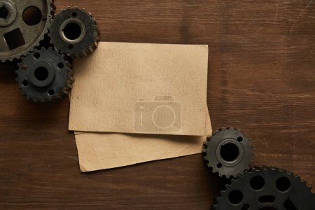 Photo for Top view of vintage paper and gears on wooden table - Royalty Free Image