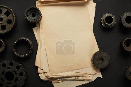 widok z góry starzejących się kół zębatych i rocznika pusty papier na czarnej powierzchni
