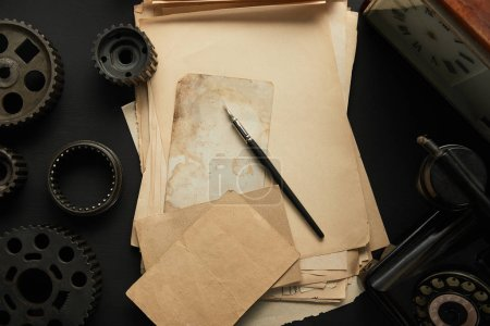 Photo for Top view of aged gears and vintage blank paper with fountain pen on black surface - Royalty Free Image