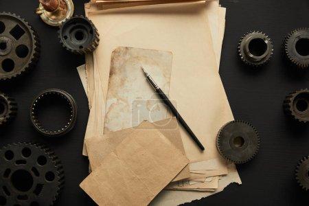 widok z góry starzejących się kół zębatych i vintage pusty papier z piórem fontanny na czarnej powierzchni