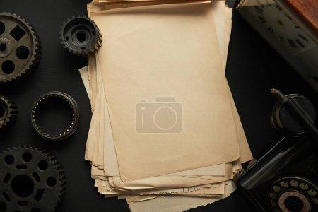 Photo pour Top view of aged gears and vintage blank paper near vintage clock on black surface - image libre de droit