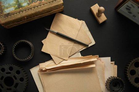 Photo pour Vue du dessus des engrenages vieillis, papier blanc vintage avec stylo plume près du timbre, peinture et horloge sur surface noire - image libre de droit