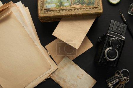Photo pour Top view of vintage camera, paper, painting, fountain pen, keys on black background - image libre de droit