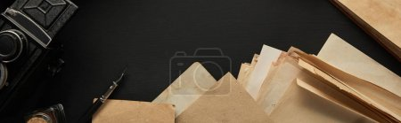 Photo pour Top view of vintage camera, paper, fountain pen on black background, panoramic shot - image libre de droit