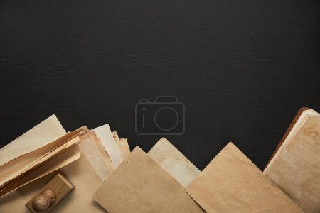 Photo pour Top view of vintage paper and stamp on black background - image libre de droit