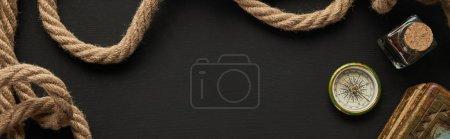 Photo pour Vue de dessus du papier vintage, corde, boussole et peinture sur fond noir, panoramique - image libre de droit