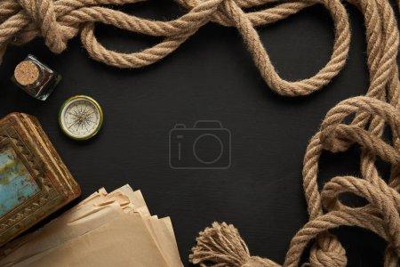 Foto de Vista superior del papel antiguo, cuerda, brújula y pintura sobre fondo negro. - Imagen libre de derechos