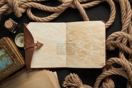 Foto de Vista superior del cuaderno vintage, cuerda, brújula y pintura sobre fondo negro. - Imagen libre de derechos