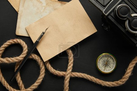 Photo for Top view of vintage camera, paper, rope, fountain pen, compass on black background - Royalty Free Image