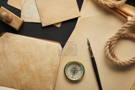 Photo pour Vue du dessus du papier vintage, corde, boussole, timbre et stylo plume sur fond noir - image libre de droit