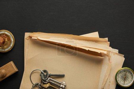 Photo pour Vue du dessus du papier vintage, clés, boussole et timbre sur fond noir - image libre de droit