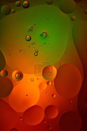 abstrakter Hintergrund aus gemischten Wasser- und Ölblasen in grüner und roter Farbe