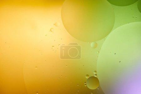 Foto de Hermoso fondo abstracto de agua y aceite mezclados en color púrpura, naranja y verde. - Imagen libre de derechos