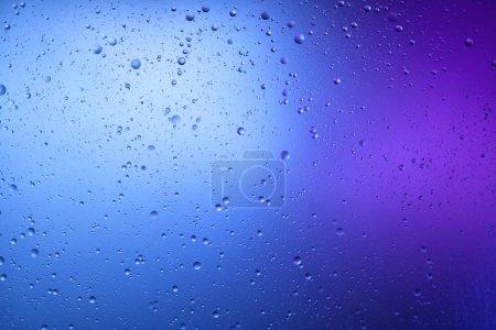 Foto de Hermoso fondo abstracto de agua y aceite mezclados en azul y color púrpura. - Imagen libre de derechos