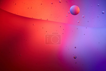 creative abstract texture from mixed water and oil bubbles in pink and purple color