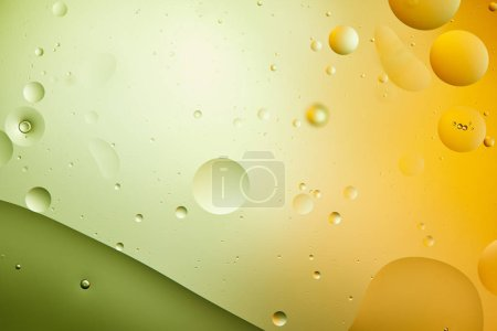 abstract creative background from mixed water and oil in green and orange color
