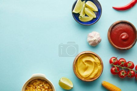 Photo for Top view of lime, mustard with tomato sauce and vegetables on blue background - Royalty Free Image