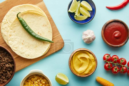 Photo for Top view of tortillas on cutting board with taco ingredients on blue background - Royalty Free Image