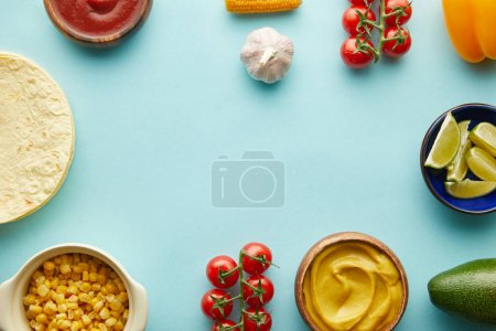 Photo for Top view of tortillas with taco ingredients on blue background - Royalty Free Image