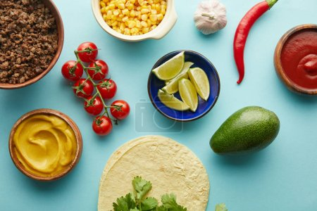 Photo for Fresh tortillas with taco ingredients, mustard and tomato sauce on blue background - Royalty Free Image