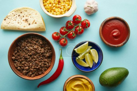Photo for Top view of fresh ingredients for taco with meat on blue background - Royalty Free Image