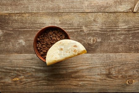 Photo for Top view of tortilla on bowl with minced meat on wooden background - Royalty Free Image
