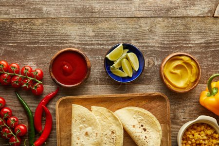 Photo for Top view of ripe vegetables, tortillas and sauces on wooden background - Royalty Free Image