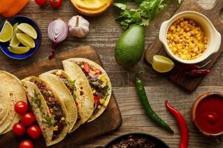 Photo for Top view of traditional mexican tacos with organic ingredients on wooden background - Royalty Free Image