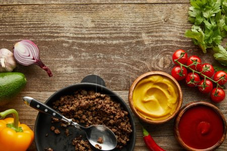 Photo for Top view of minced meat in frying pan with sauces and raw vegetables on wooden background - Royalty Free Image