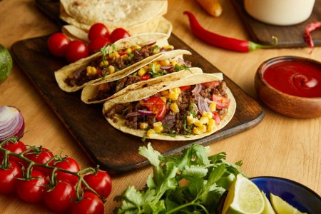 Photo for Traditional mexican tacos with vegetables and parsley on wooden table - Royalty Free Image