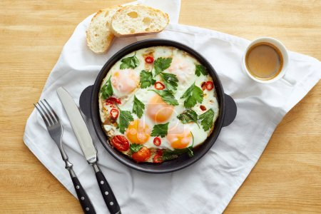 Photo for Top view of fried eggs in pan near bread, cutlery, coffee on napkin on wooden table - Royalty Free Image
