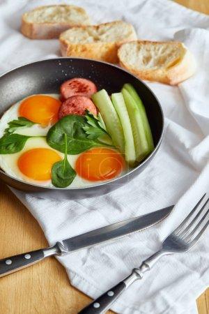 Photo pour Foyer sélectif des œufs frits dans une poêle aux épinards, concombre et saucisse à table en bois avec couverts et pain sur serviette - image libre de droit