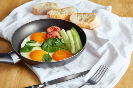 Photo for Selective focus of fried eggs in frying pan with spinach, cucumber and sausage at wooden table with cutlery and bread on napkin - Royalty Free Image