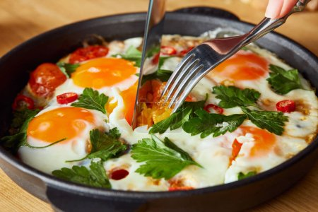 Photo for Cropped view of eating fried eggs with parsley and chili pepper on wooden table with fork and knife - Royalty Free Image