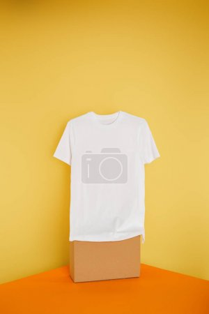Photo for Basic white t-shirt on cube on yellow background - Royalty Free Image