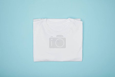 Photo for Top view of blank basic white t-shirt isolated on blue - Royalty Free Image