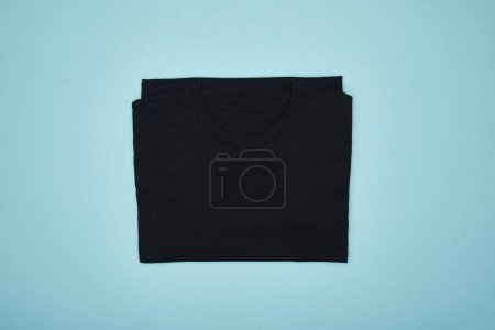 top view of blank basic black t-shirt isolated on blue