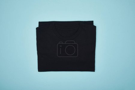 Photo for Top view of blank basic black t-shirt isolated on blue - Royalty Free Image