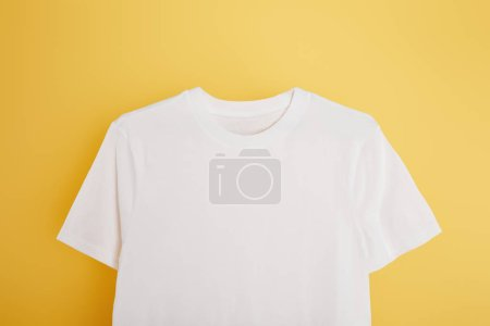top view of basic white t-shirt on yellow background