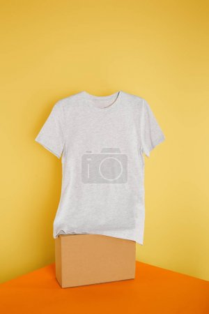 Photo for Basic grey t-shirt on cube on yellow background - Royalty Free Image