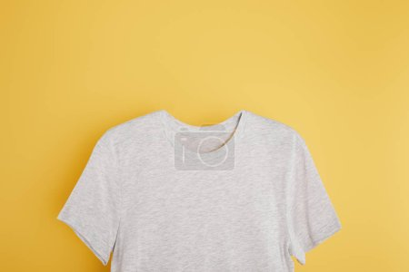 Photo for Top view of basic grey t-shirt on yellow background - Royalty Free Image