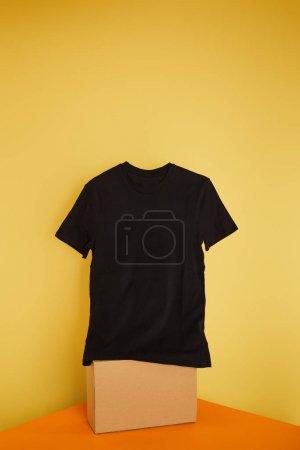 basic black t-shirt on cube on yellow background