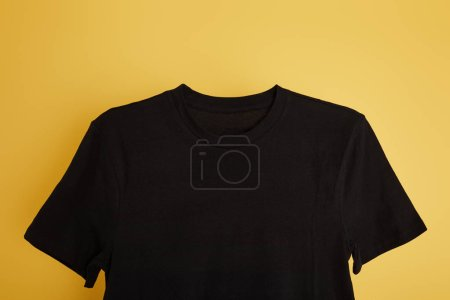 top view of basic black t-shirt on yellow background