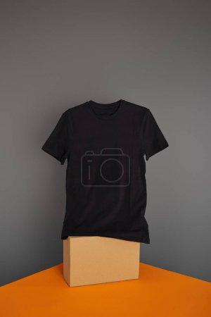 basic black t-shirt on cube on grey and orange background