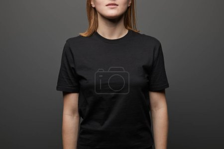 Photo for Cropped view of woman in blank basic black t-shirt on black background - Royalty Free Image