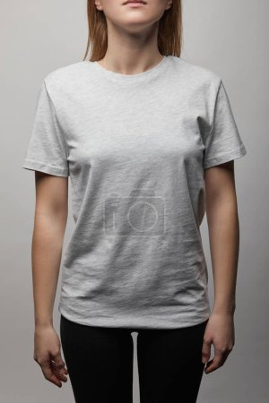 cropped view of woman in blank basic grey t-shirt on grey background