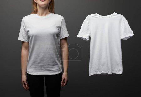 Photo pour Vue recadrée de la femme près de blanc de base t-shirt blanc sur fond noir - image libre de droit