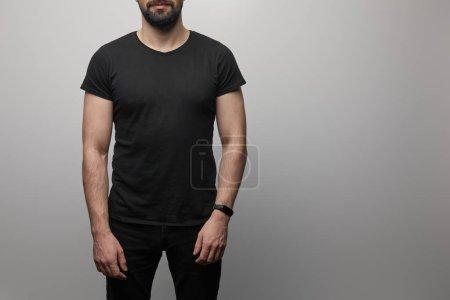 Foto de Vista cropeada del hombre portador en blanco camiseta negra básica sobre fondo gris. - Imagen libre de derechos